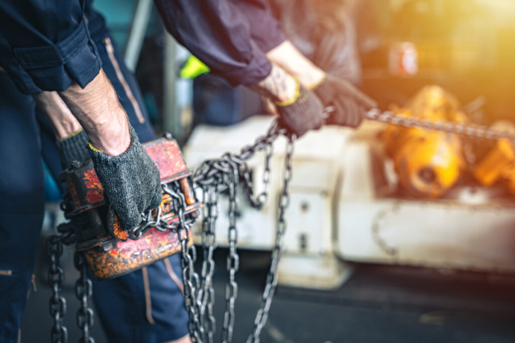 construction workers pulling a chain attached to a hoist