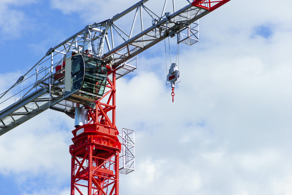 red and gray tower crane with blue sky background