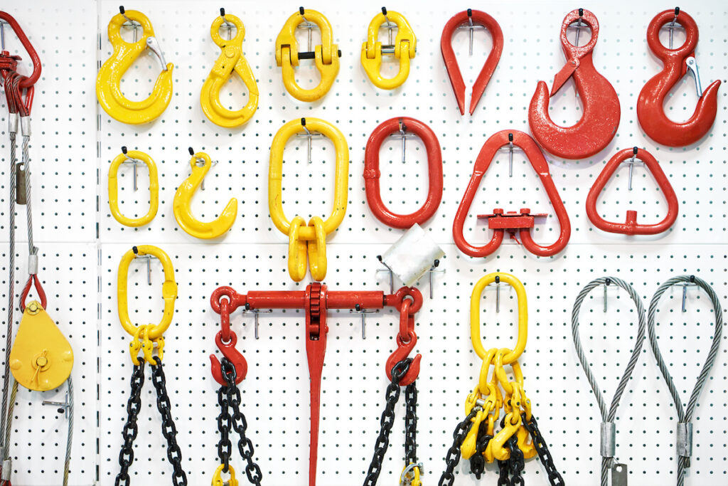 white wall with hanging hooks, blocks and hoist chains