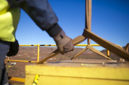 Blurry rigger hand holding a three tone lifting sling to control, stabilising the load prior crane is lifting at construction site, Perth, Australia